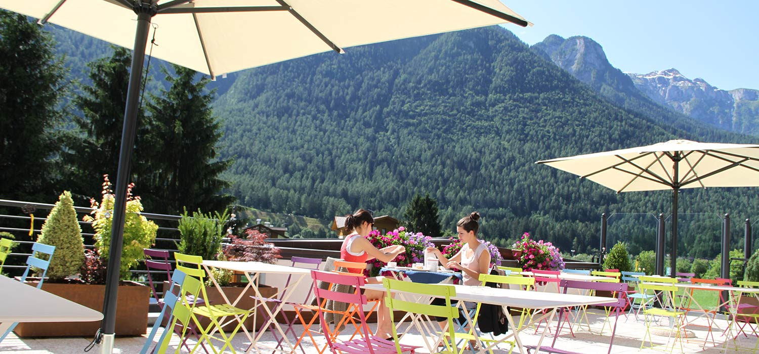 he terrace at the Hotel Ariston in Trentino on a sunny day: sun umbrellas protect guests from the sun.