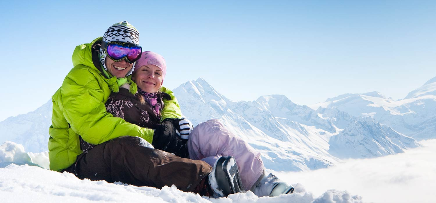 A couple in full skiwear while hugging, sitting in the snow.